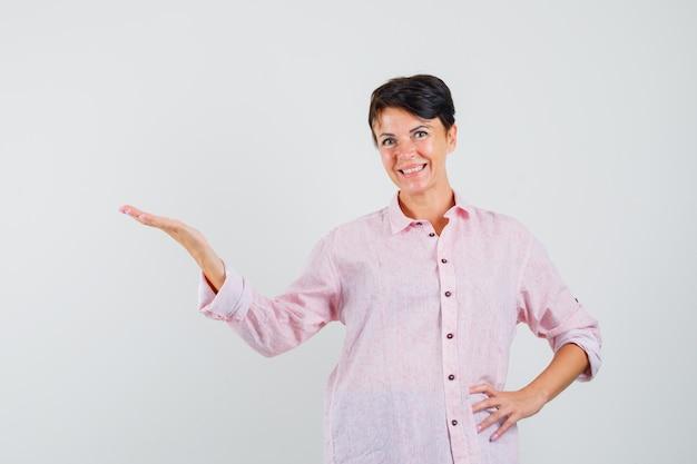Mujer en camisa rosa dando la bienvenida o mostrando algo y mirando alegre, vista frontal.