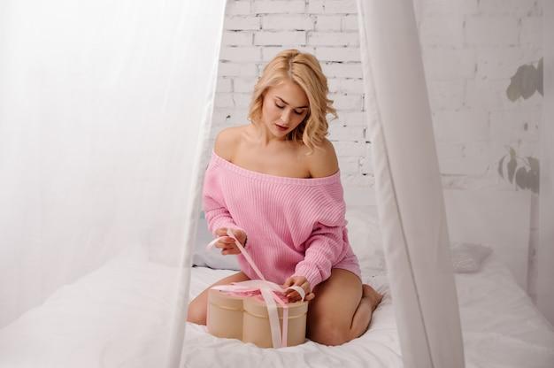 Mujer con camisa rosa sentada en la cama con la caja de flores