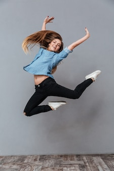 Mujer en camisa saltando en studio