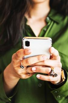 Mujer en camisa de seda verde con un teléfono inteligente