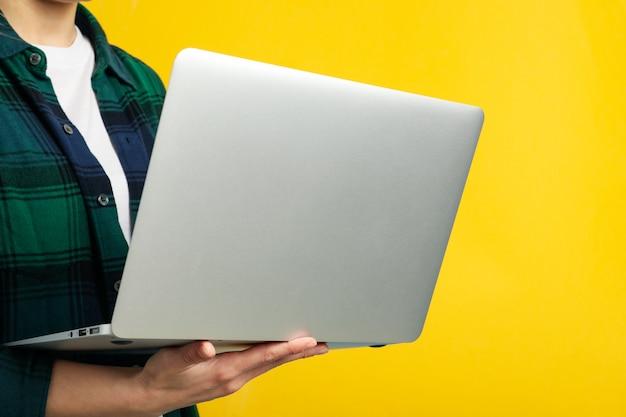 Mujer en camisa tiene laptop sobre superficie amarilla