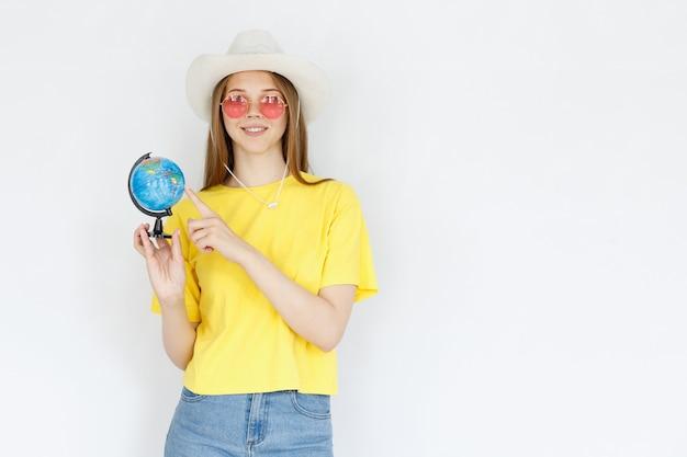 Una mujer con una camiseta amarilla se muestra en el mundo sobre un fondo gris. vacaciones y turismo