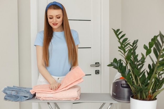 Mujer en una camiseta azul planchado en casa