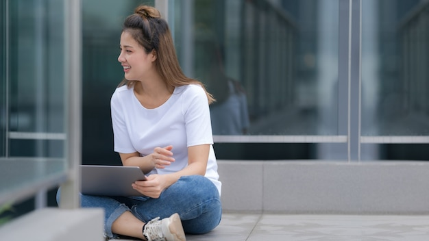 Mujer en camiseta blanca y jeans usando laptop sentada en un piso afuera en el fondo de la calle de la ciudad, día de verano