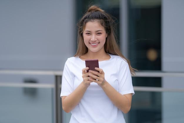 Mujer en camiseta blanca y jeans usando teléfono de pie en un piso afuera en el fondo de la calle de la ciudad, día de verano
