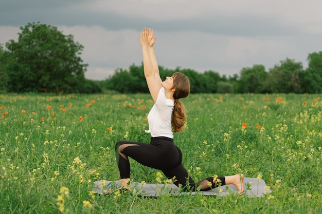 Mujer en una camiseta blanca y leggings haciendo yoga en un hermoso campo en un estilo de vida de estera deportiva