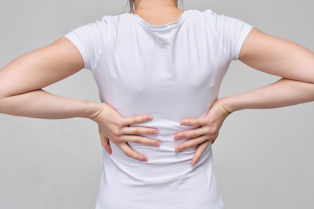 Una mujer de camiseta blanca con las manos masajea la espalda, la espalda baja. dolor muscular y columna vertebral.