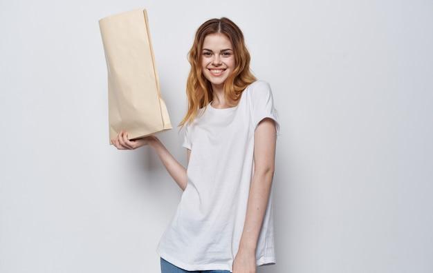 Mujer en camiseta blanca con un paquete de compras de embalaje de comestibles