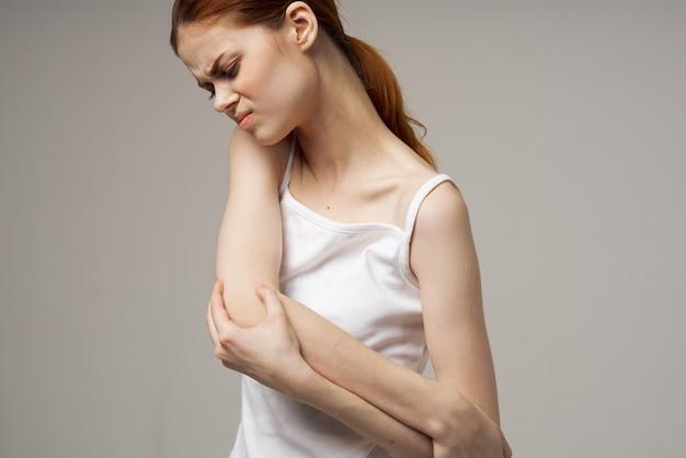 Mujer en camiseta blanca reumatismo dolor en el codo problemas de salud fondo claro