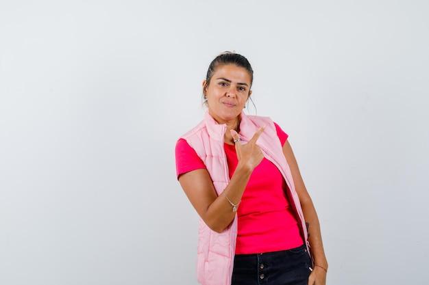 Mujer en camiseta, chaleco apuntando a la esquina superior derecha y luciendo sensato