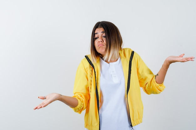 Mujer en camiseta, chaqueta mostrando gesto de impotencia y mirando confundido, vista frontal.