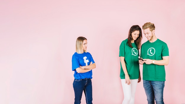 Mujer en camiseta de facebook mirando pareja feliz usando teléfono móvil