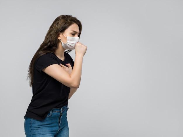 Mujer en camiseta negra y jeans azul tosiendo