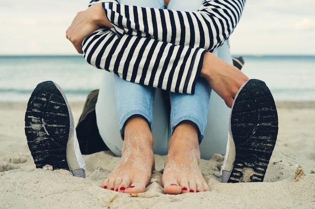 Mujer en camiseta a rayas y pantalones vaqueros se sienta descalza en la playa al lado de los zapatos