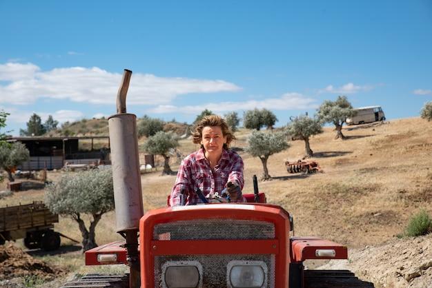 Mujer campesina conduciendo un tractor en el campo