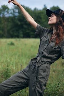 Mujer en el campo el aire fresco se mantiene en un mono verde resto