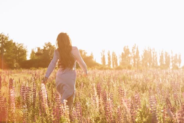 Mujer en el campo de flor de la puesta del sol.