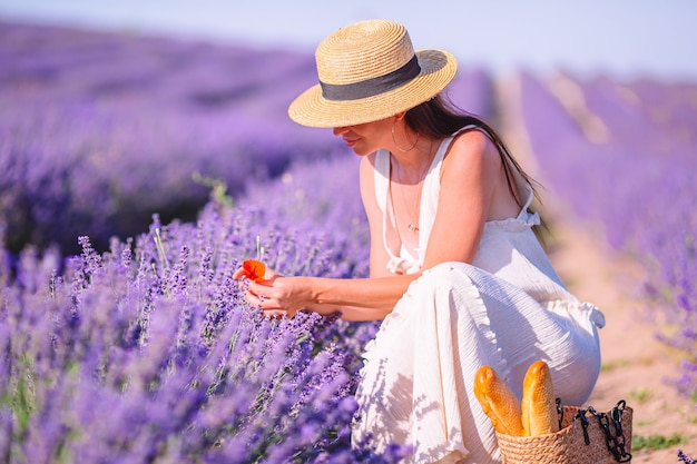 Mujer en campo de flores de lavanda al atardecer en vestido blanco y sombrero