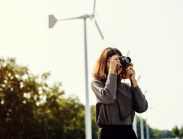Mujer en el campo del molino de viento tomando una foto