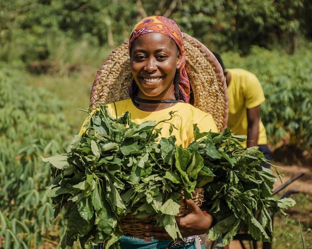 Mujer de campo sosteniendo hojas de plantas