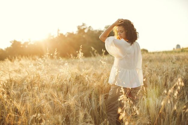 Mujer en un campo de verano. morena con camisa blanca.