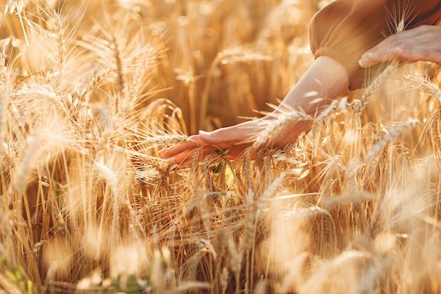 Mujer en un campo de verano. morena con un suéter marrón.