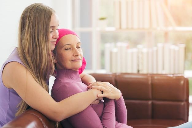 Mujer de cáncer acostada apoyada por mamá en casa. concepto de confianza y ética
