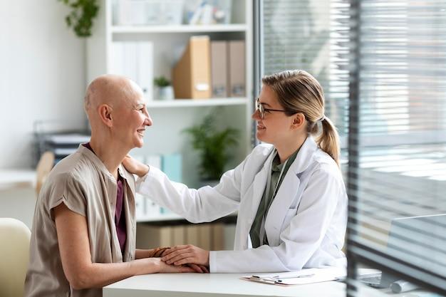 Mujer con cáncer de piel hablando con el médico Foto gratis