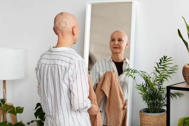 Mujer con cáncer de piel mirando en el espejo
