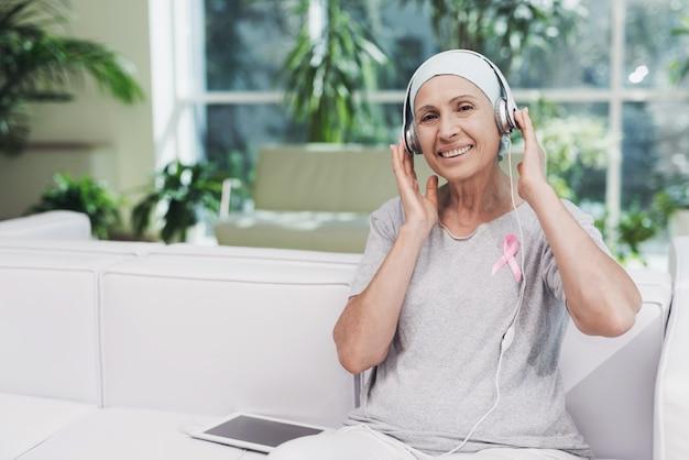 Una mujer con cáncer está sentada y escucha música en la clínica.