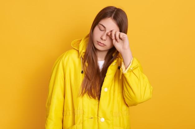 Mujer cansada con chaqueta amarilla frotándose los ojos, mujer con el pelo largo y hermoso posando con los ojos cerrados, se ve exhausta, de pie contra la pared brillante.