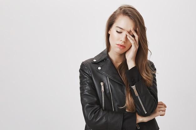 Mujer cansada con chaqueta de cuero, mirar hacia abajo, con la cara enfadada