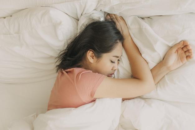 Mujer cansada descansa y duerme en su calido dormitorio.