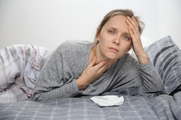 Mujer cansada enferma en la cama, con dolor de garganta, mirando a la cámara