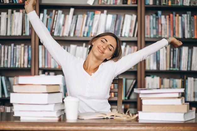 Mujer cansada estirando en la biblioteca