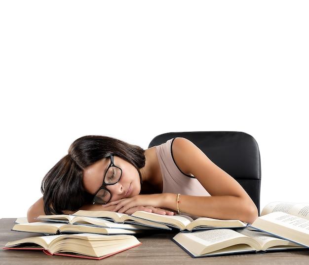 Mujer cansada de estudiar durmiendo sobre libros