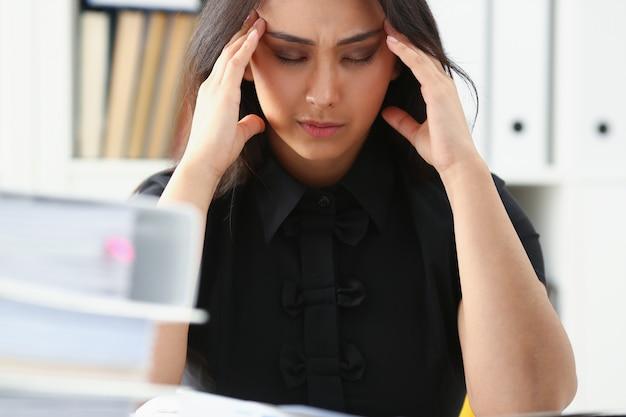 Mujer cansada y exhausta mira documentos que sostienen su cabeza con las manos
