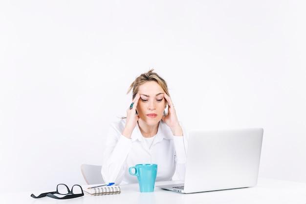 Mujer cansada frotando las sienes