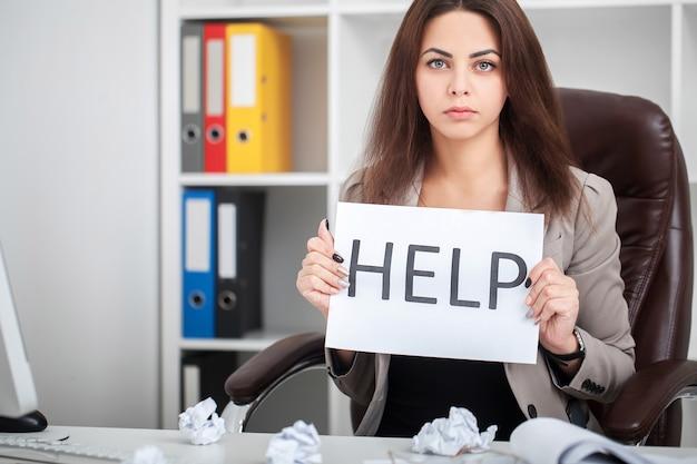 Mujer cansada y frustrada europea que trabaja como secretaria en estrés en el escritorio de la oficina del distrito comercial de trabajo con computadora portátil pidiendo ayuda en concepto de frustración