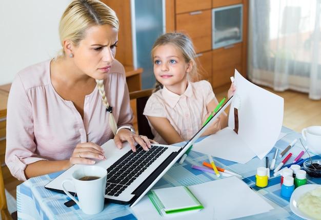 Mujer cansada con hija trabajando en línea