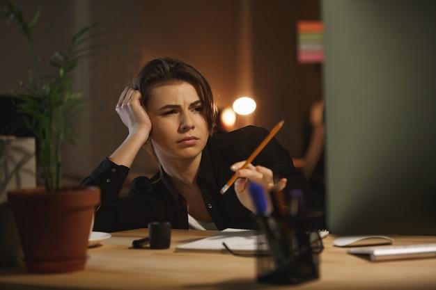 Mujer cansada con lápiz trabajando con computadora
