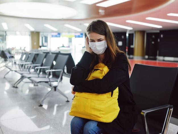 Mujer cansada en máscara médica con retraso de vuelo de espera de aeropuerto de equipaje
