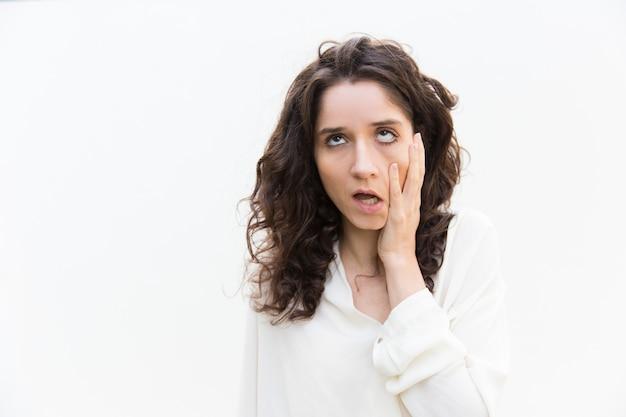 Mujer cansada molesta tocando la mejilla, mirando hacia arriba