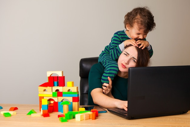 Mujer cansada con un niño en el cuello sentado frente a una computadora y hablando por teléfono con el empleador mientras el niño juega cubos y la rodea.