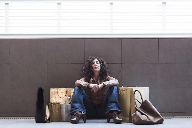 Mujer cansada que se sienta con los bolsos de compras en la calle