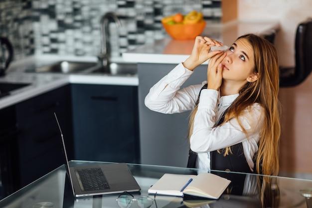 Mujer cansada que siente fatiga ocular después de un uso prolongado de la computadora portátil sentada en casa