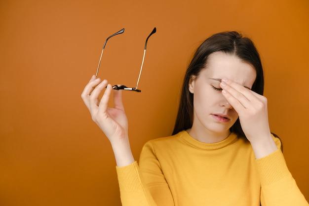 Mujer cansada quitándose gafas