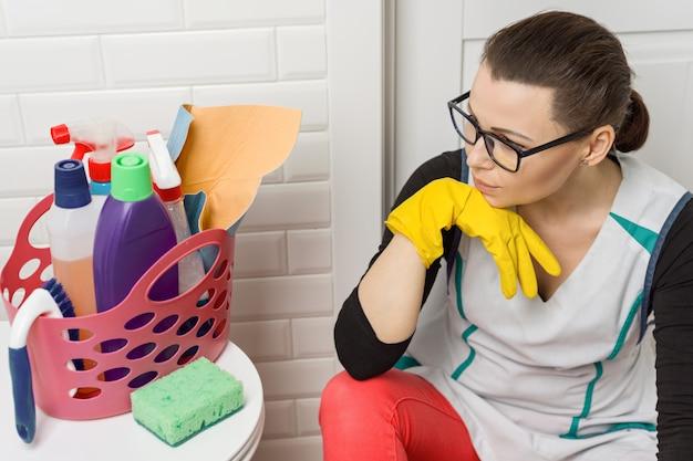 Mujer cansada sentada en el piso del baño con productos de limpieza