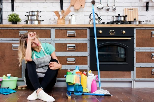 Mujer cansada sentada en el piso de la cocina con productos y equipos de limpieza