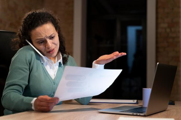 Mujer cansada trabajando hasta tarde por un plazo